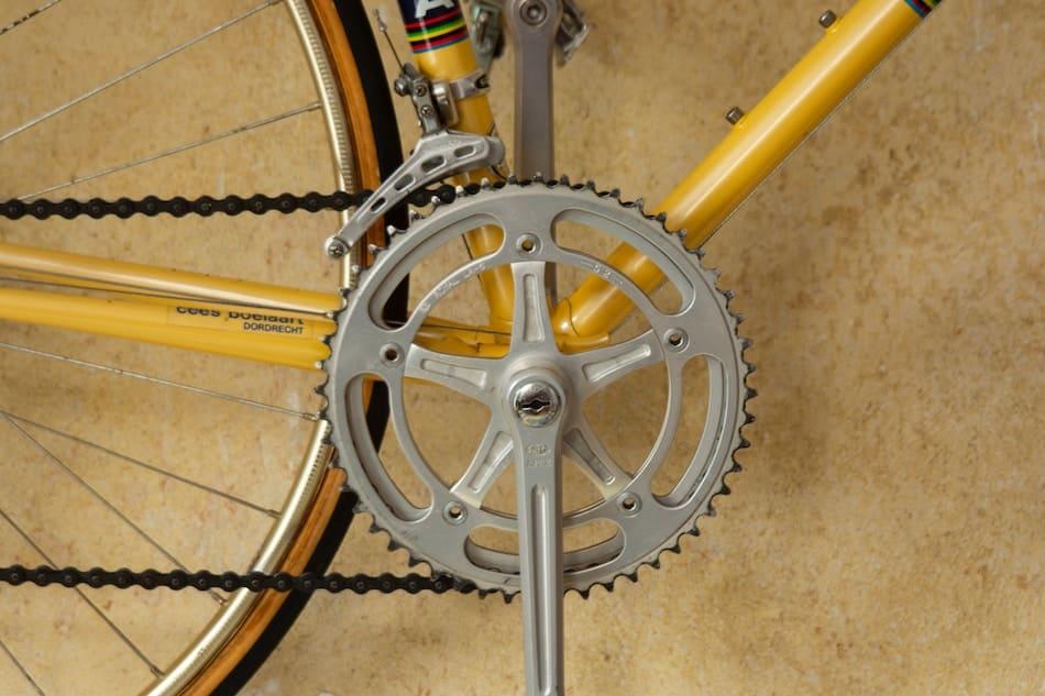 Elegir los componentes de la bicicleta. Detalle de una catalina y una bicicleta de carretera amarilla antigua