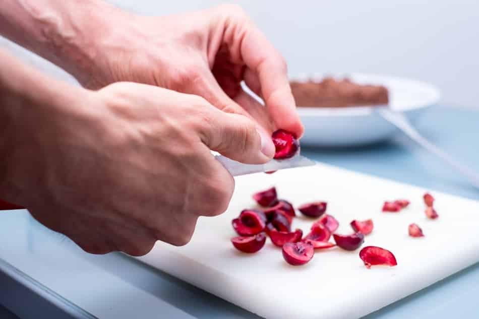 Sacando el hueso de las cerezas para hacer la mermelada cruda.