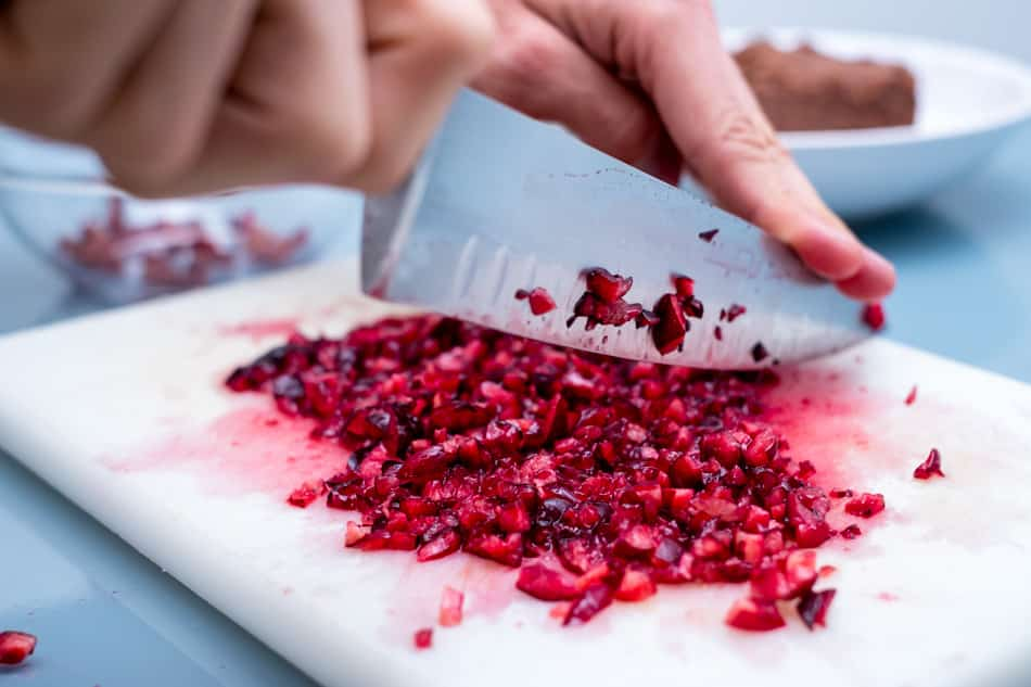 Picando las cerezas para hacer la mermelada cruda para el desayuno con polenta saludable.